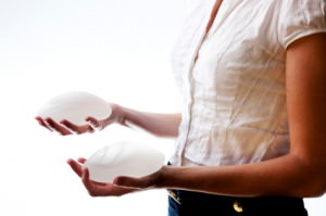 safety of silicone gel breast implants, woman holding implants